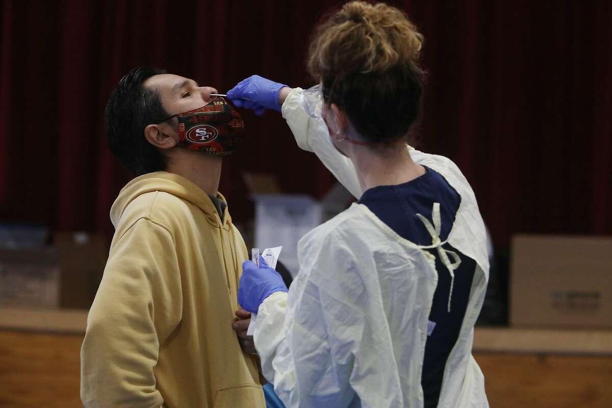Erin Daly (à direita) apresenta um pano para o teste COVID-19 a Marco Garcia de San Jose na Igreja Batista Emmanuel em San Jose.  A vacina tornou-se ainda mais importante à medida que surgiram mutações no vírus, abrindo um caminho mortal pelo Brasil.