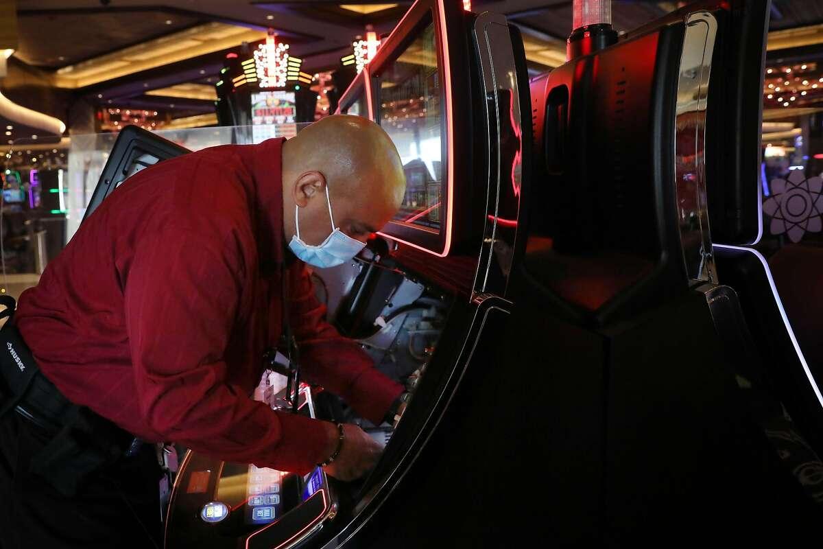 Shanti Duroux, guest services ambassador, troubleshoots an error while changing the cash-out voucher paper on a machine.