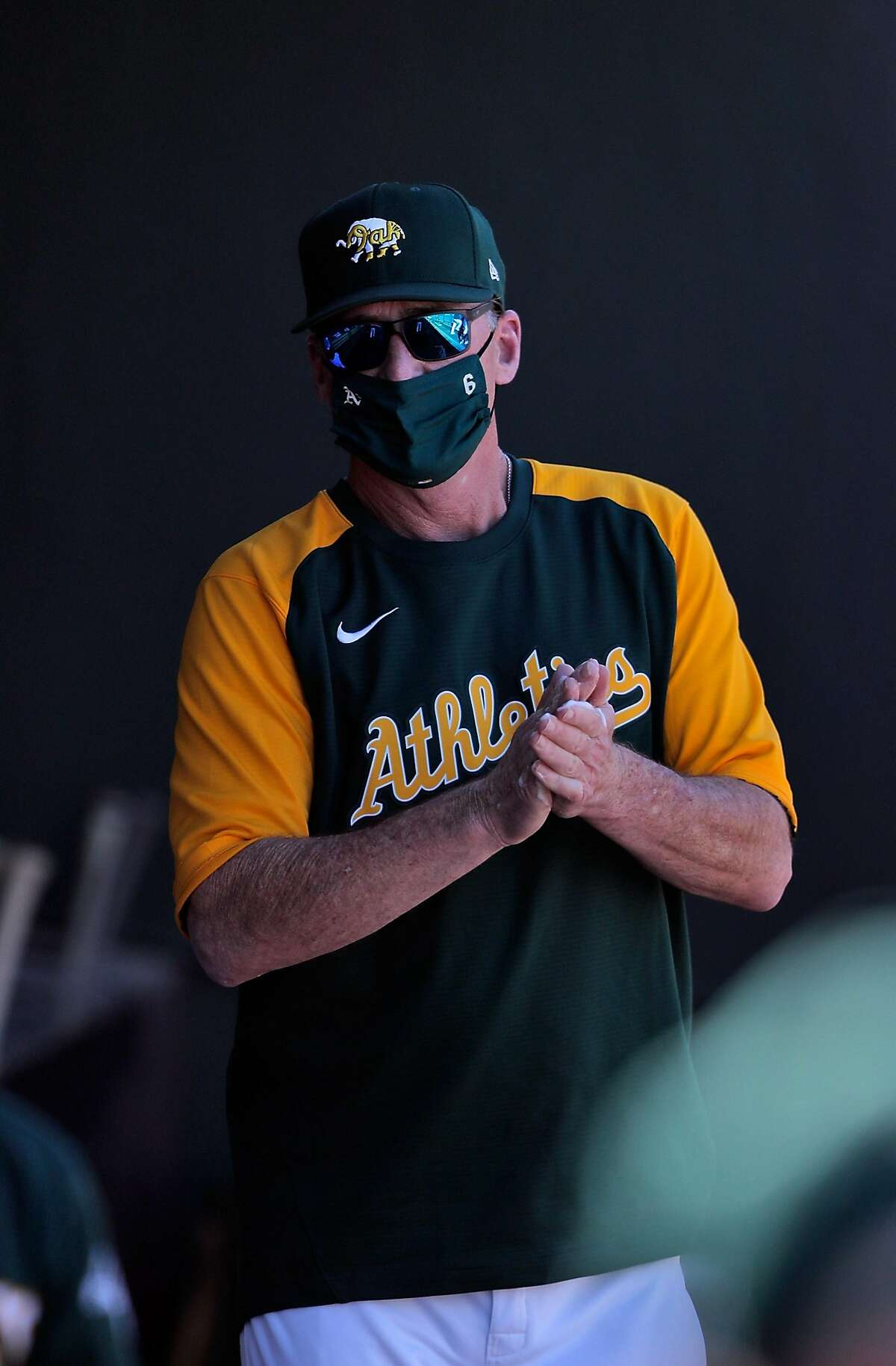 A's manager Bob Melvin sanitizes his hands in the dugout as the Oakland Athletics played the Cincinnati Reds at Hohokam Stadium in Mesa, Ariz., on Monday, March 1, 2021.