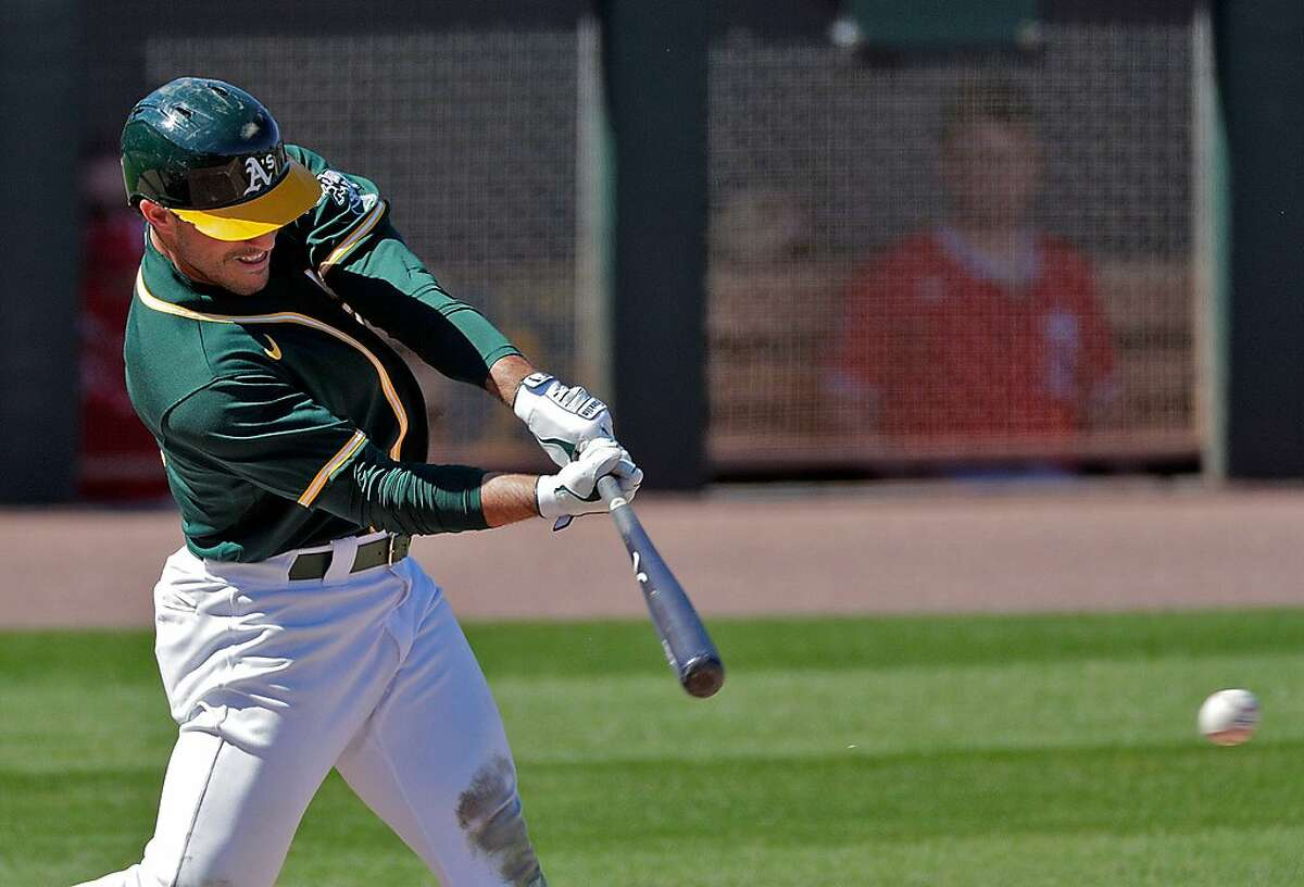 Ramon Laureano (22) hits a double in the second inning as the Oakland Athletics played the Los Angeles Angels at Hohokam Stadium in Mesa, Ariz., on Friday, March 5, 2021.