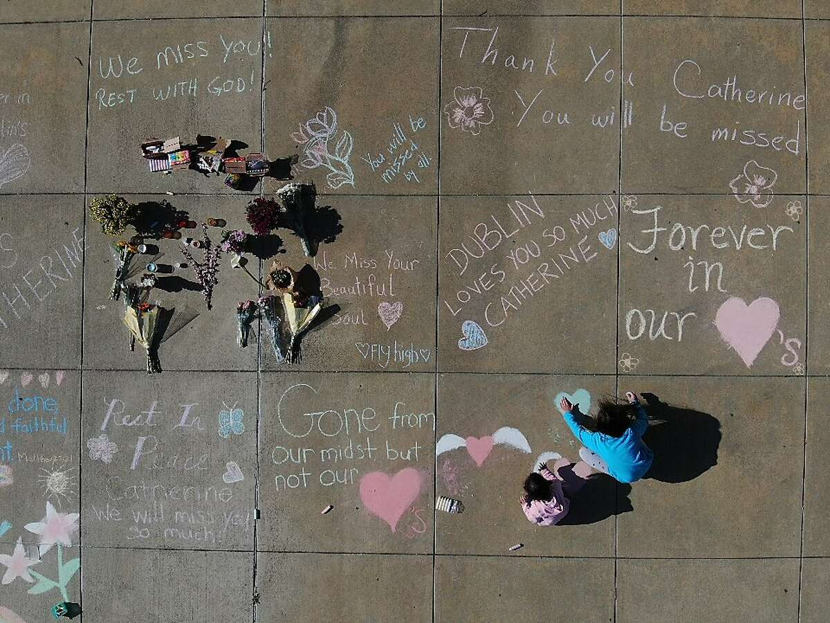 Jessie Burroughs, 6, and sister Sammie Burroughs, 10, (blue) add to the memorial for Catherine Kuo, a Dublin school board member who was killed by a driver picking up food during a food distribution event on Thursday, March 25, 2021 in Dublin, Calif.