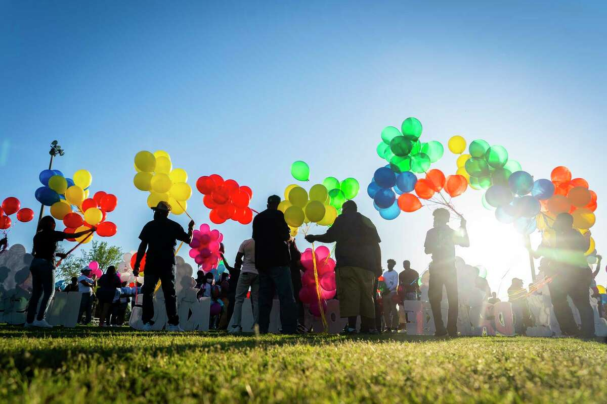 Family and friends of Porsha Branch, who was killed by a drunk driver along with her three young children, Drake, King and Messiah, prepare to release balloons during a vigil for the family on Thursday evening, March 25, 2021, at Meyer Park in Spring.