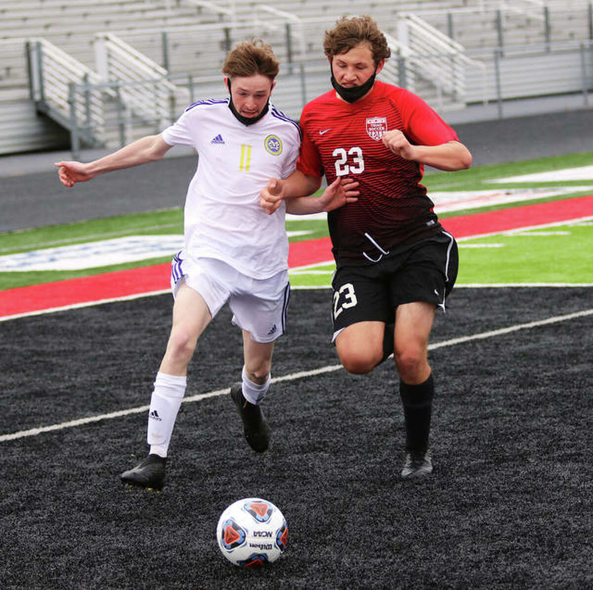 CM's Zach Depping (left) is unable to get past Triad's Lee Beeman and keep the ball from rolling past the end line on Triad' side of the field in the first half Thursday in Troy.