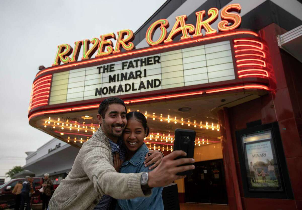 """Jeet Singh and Rubi Morgan take a selfie with the River Oaks Theatre marquee after watching """"Minari"""" on the second last day of the theater Wednesday, March 24, 2021, in Houston. The pair was going to buy tickets of the last screening of the theater, but the show was sold out so they picked the second last day."""