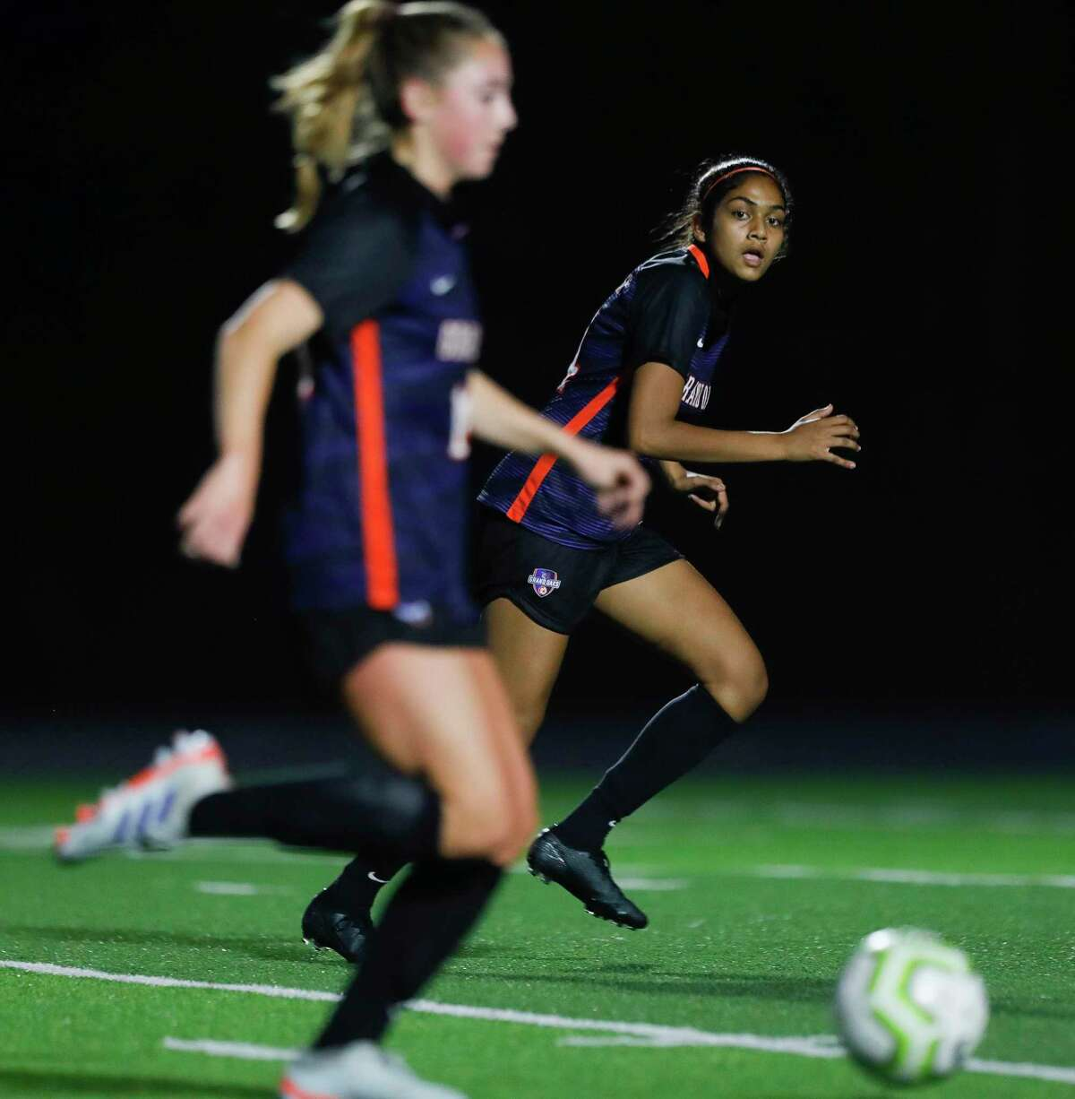Shown here earlier this season, Grand Oaks forward Veronica Patel (14), right, and Reese Rupe (18) each scored two goals Thursday night as the Grizzlies won their first-ever playoff game over Aldine Davis in Region II-6A.