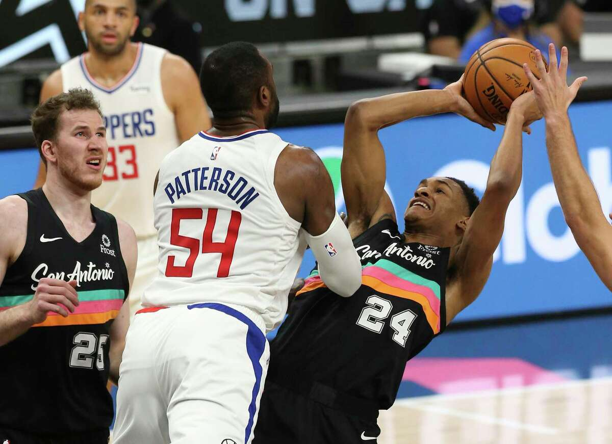Spurs' Devin Vassell (24) gets fouled by the Los Angeles Clippers' Patrick Patterson (54) while going for a shot at the AT&T Center on Thursday, Mar. 25, 2021.