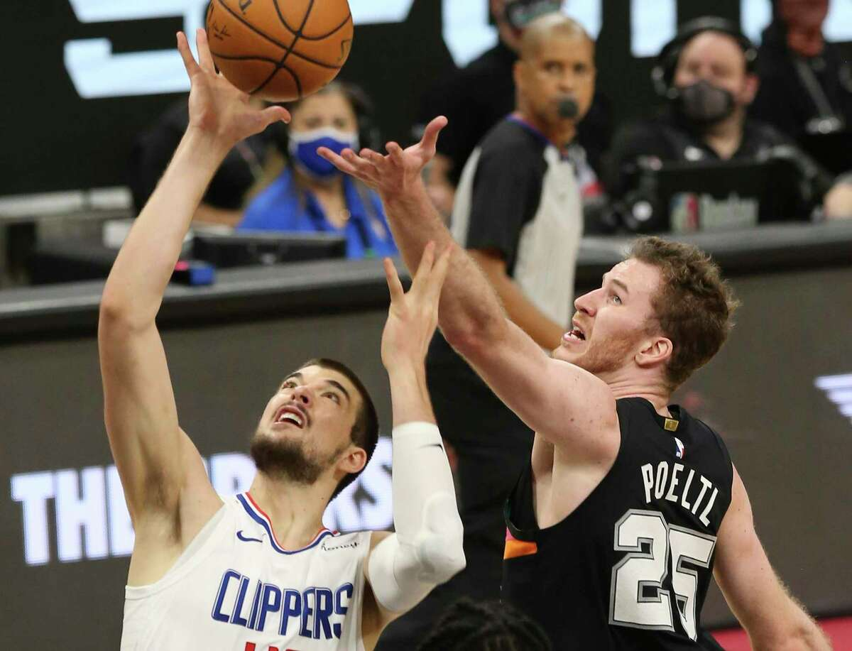 Spurs' Jakob Poeltl (25) battles for a rebound against the Los Angeles Clippers' Ivica Zubac (40) at the AT&T Center on Thursday, Mar. 25, 2021.