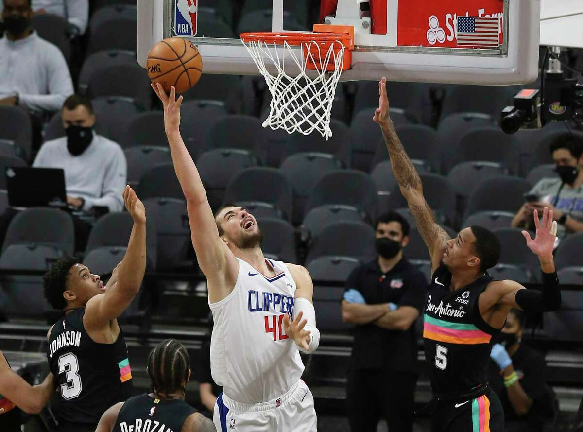Los Angeles Clippers' Ivica Zubac (40) attempts a shot in the paint against Spurs' Dejounte Murray (05) and Keldon Johnson (03) at the AT&T Center on Thursday, Mar. 25, 2021.