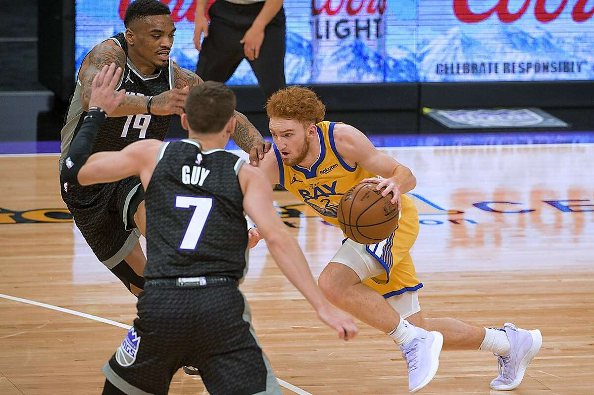 Sacramento Kings guard DaQuan Jeffries (19) guard Kyle Guy (7) defend against Golden State Warriors guard Nico Mannion (2) during the first quarter of an NBA basketball game in Sacramento, Calif., Thursday, March 25, 2021. (AP Photo/Randall Benton)