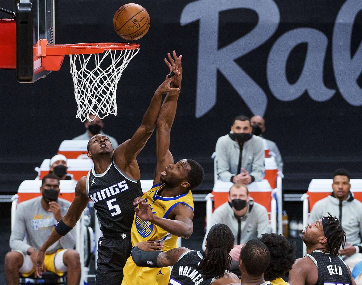 Warriors forward Andrew Wiggins lays the ball up as Sacramento Kings guard De'Aaron Fox (5) defends during the first quarter of an NBA basketball game in Sacramento, Calif., Thursday, March 25, 2021. (AP Photo/Randall Benton)