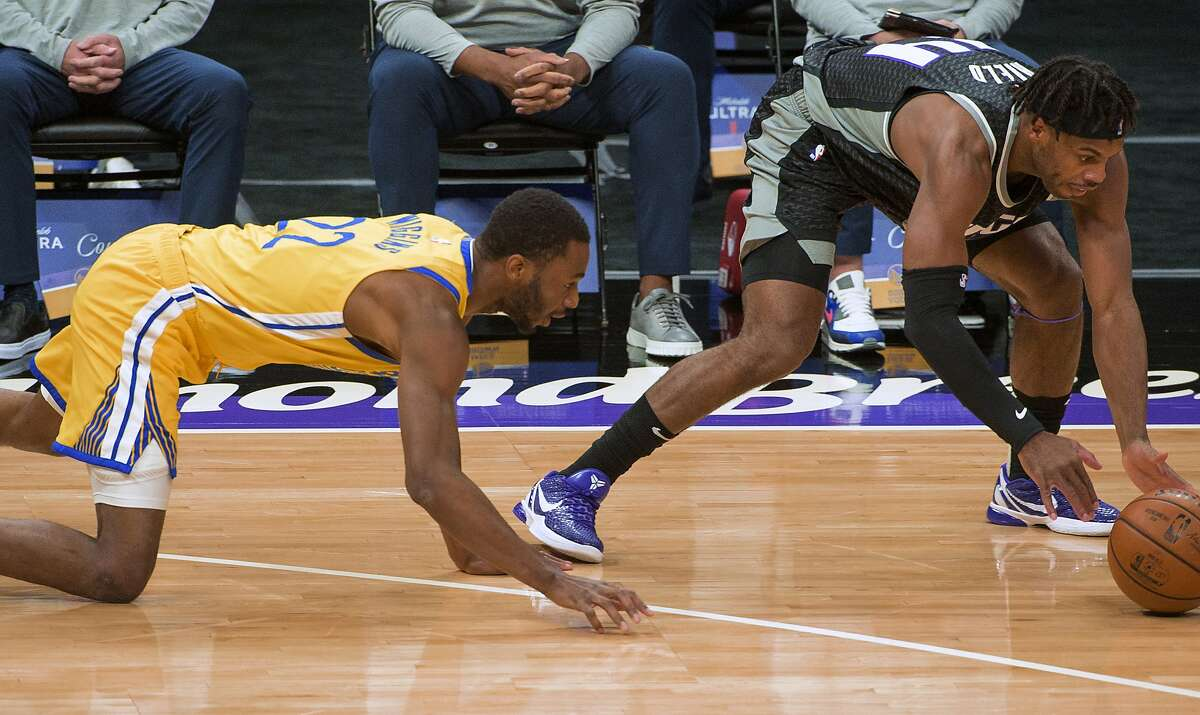 Golden State Warriors forward Andrew Wiggins (22) and Sacramento Kings guard Buddy Hield (24) chase the ball during the first quarter of an NBA basketball game in Sacramento, Calif., Thursday, March 25, 2021. (AP Photo/Randall Benton)