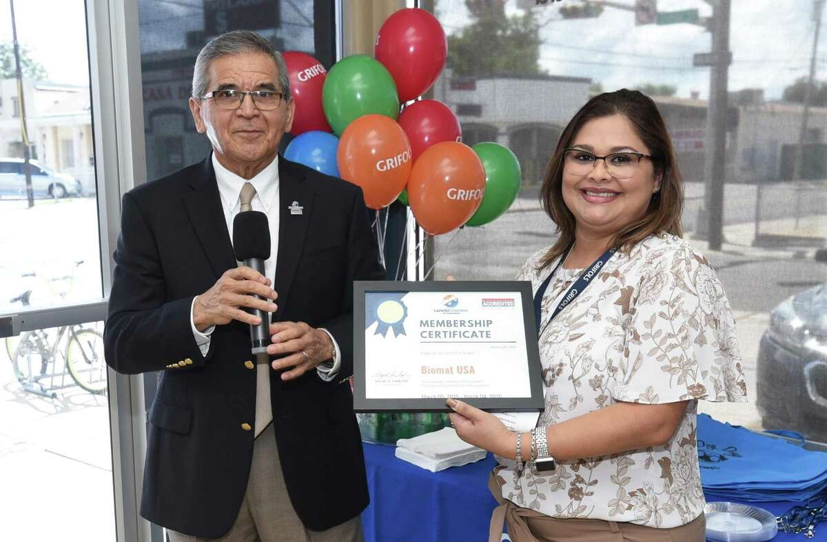 Laredo Chamber of Commerce President/CEO Miguel Conchas recognizes Site Manager Deborah Jimenez and her team with a membership certificate at Grifols Biomat USA Plasma Center during its 20th anniversary ribbon cutting, Monday, Sept. 16, 2019.