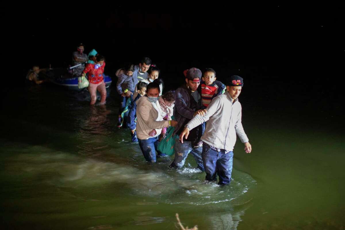 Migrant families, mostly from Central American countries, wade through shallow waters after being delivered by smugglers on small inflatable rafts on U.S. soil in Roma, Texas, Wednesday, March 24, 2021. As soon as the sun set, at least 100 migrants crossed through the Rio Grande by smugglers into the United States.