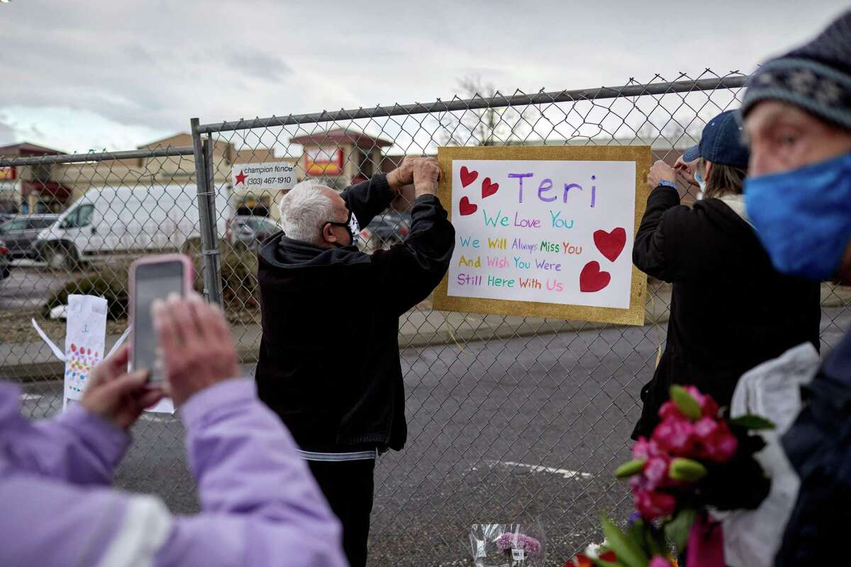 Mourners hang a memorial sign for Teri Leiker, 51, a longtime employee of King Soopers in Boulder, Colo. She died in Monday's shooting that left nine others people dead.