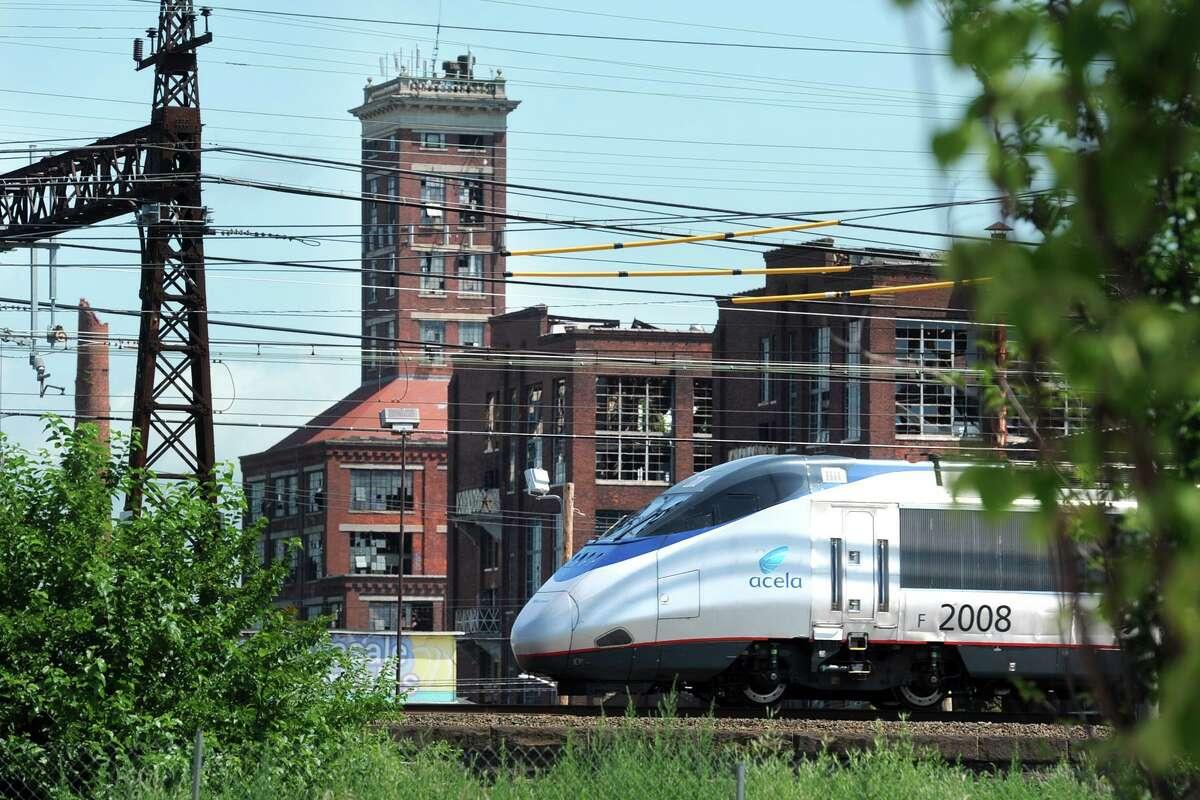 An Amtrak Acela train passes near Crescent Crossing, a new affordable housing development in Bridgeport.