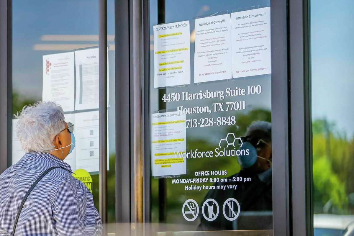 In this file photo, a woman looks at the signs saying that the Workforce Solutions office is closed due to the Covid-19 outbreak about a year ago. Texas employers in February cut jobs for the first time in 10 months.