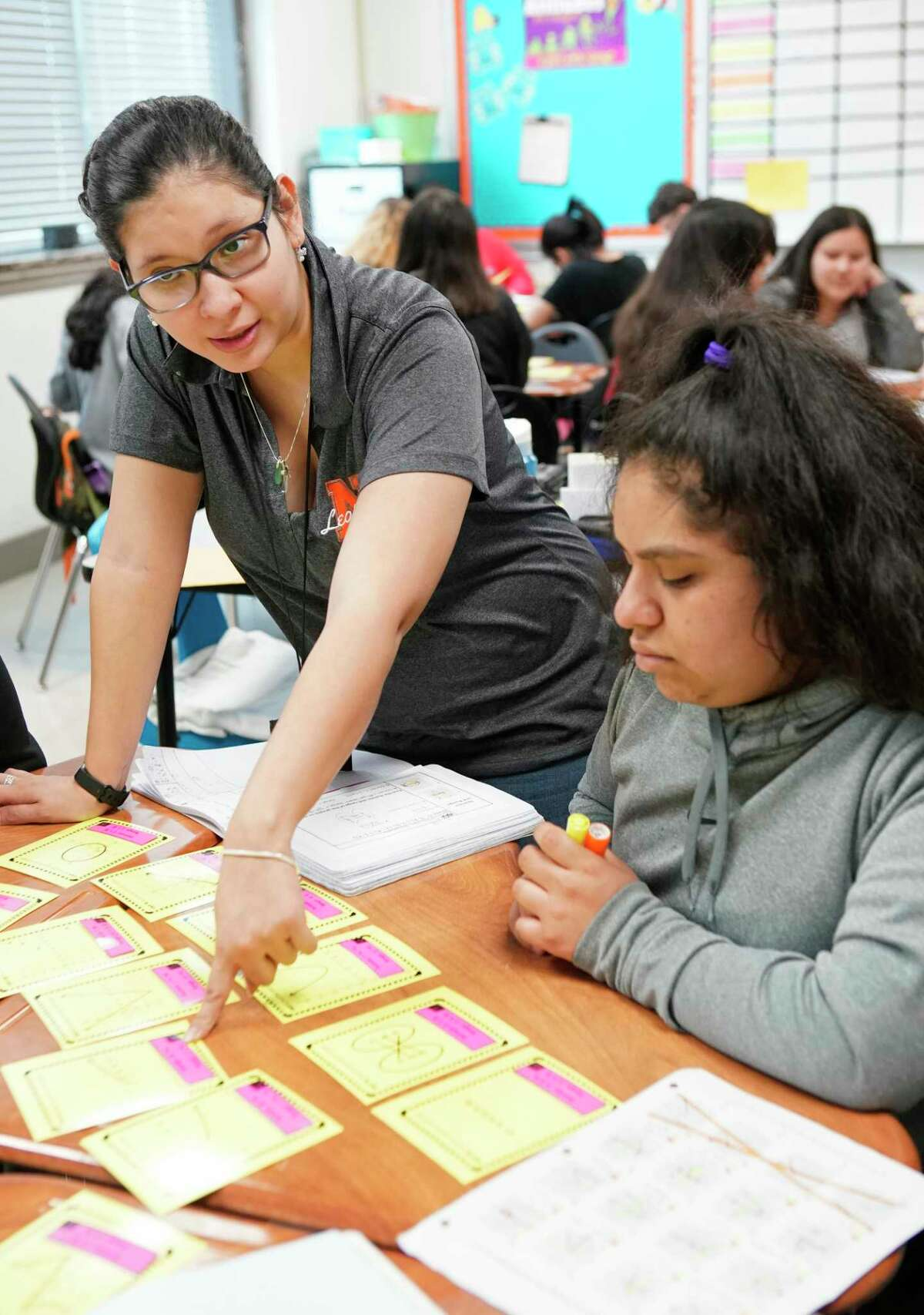 Navarro Middle School teacher Ana Steen, pictured in 2019, works with eighth-grader Jazzmin Gutierrez and others at her table during an algebra class at the Houston ISD campus. Navarro is one of 13 neighborhood middle schools that does not have a magnet program, making it harder to attract students who would bring more money to the east side campus.