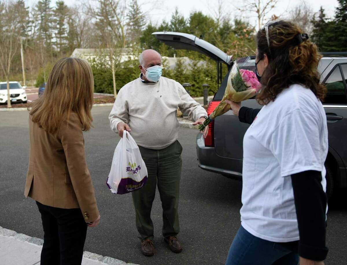 """Greenwich's Bill Zisson picks up a """"Seder Survival Kit"""" pre-wrapped by Jewish Family Services of Greenwich at Greenwich Reform Synagogue in Cos Cob on Thursday. The plates include Seder dinner essentials to help congregants celebrate Passover during a time when COVID-19 risks linger and families might not be able to gather."""