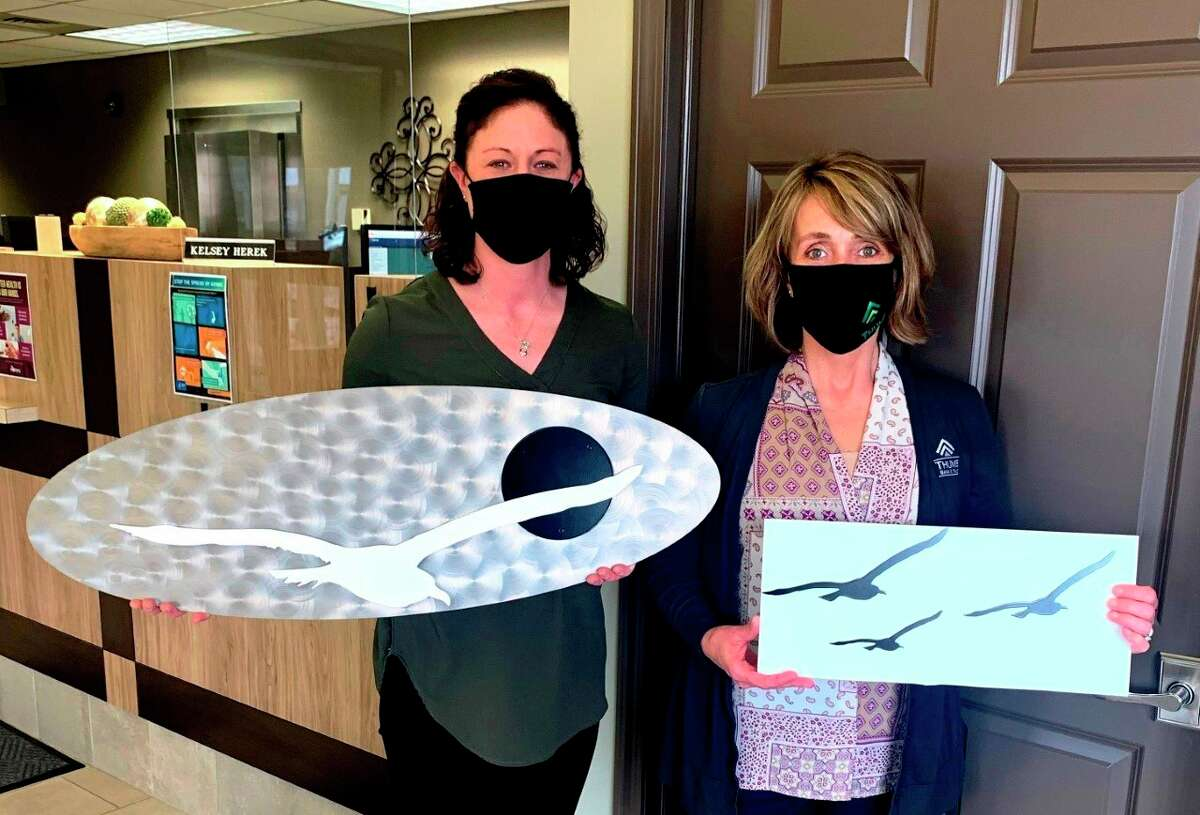 Danielle McKimmy, the community outreach coordinator for Thumb Industries, and Heather Drabek of Thumb Bank & Trust with metal seagull fabrications. The fabrications are part of Thumb Industries Soar High fundraising campaign. (Courtesy Photo/Thumb Industries)