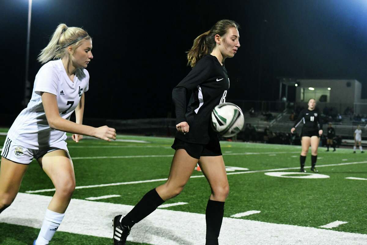 Kingwood Park junior forward Rina Lawrence, right, works the ball away from Lake Creek junior forward Jordan Venables (7) during their District 20-5A matchup at KPHS on Jan. 21, 2020.