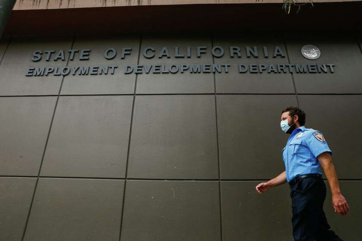 A man walks by the Employment Development Department' San Francisco office in 2020. A prison inmate, a nurse and a car dealer employee used the dark web to bilk California's troubled unemployment system of almost $2 million.