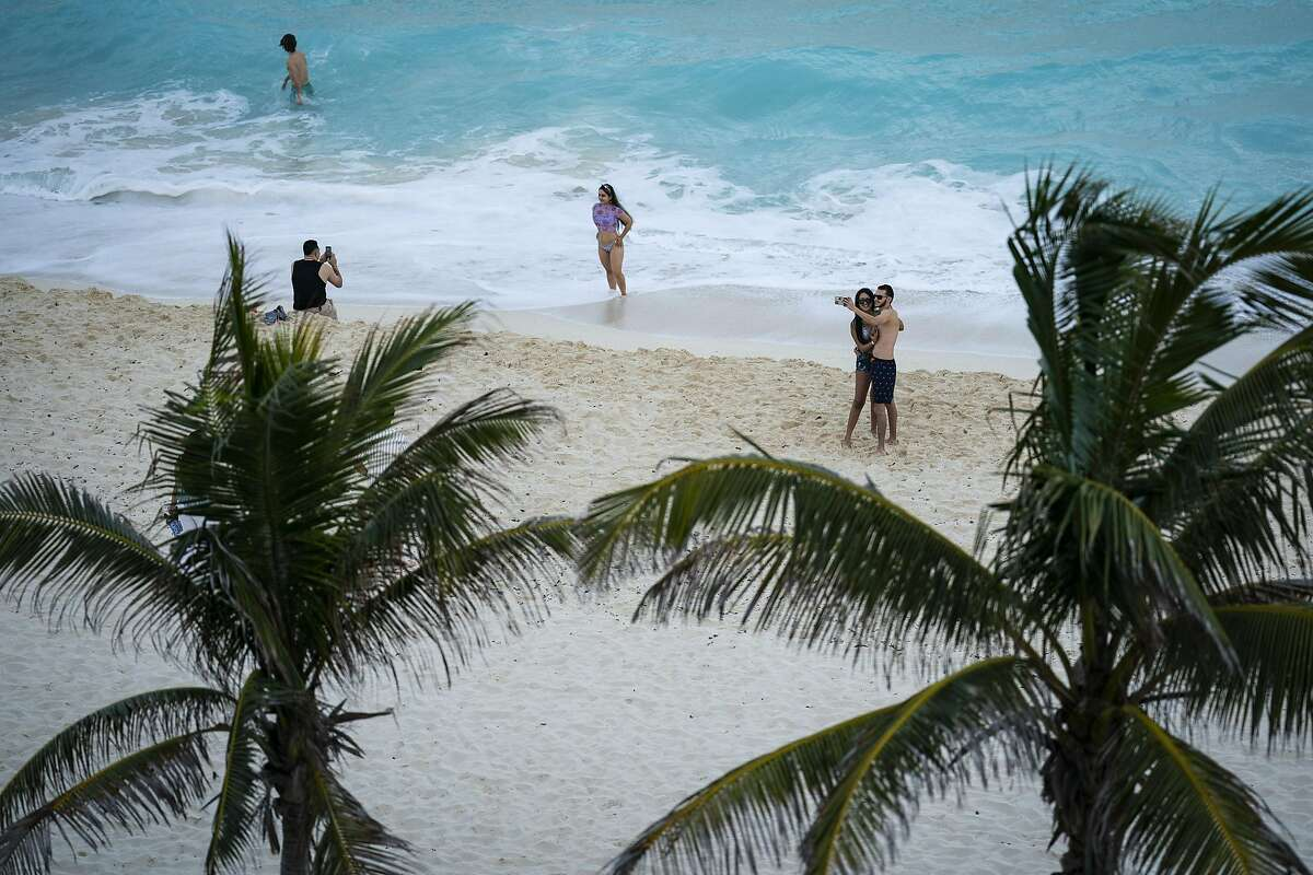 Beachgoers take to the sand and surf in Cancún, Mexico. MUST CREDIT: Washington Post photo by Jabin Botsford.