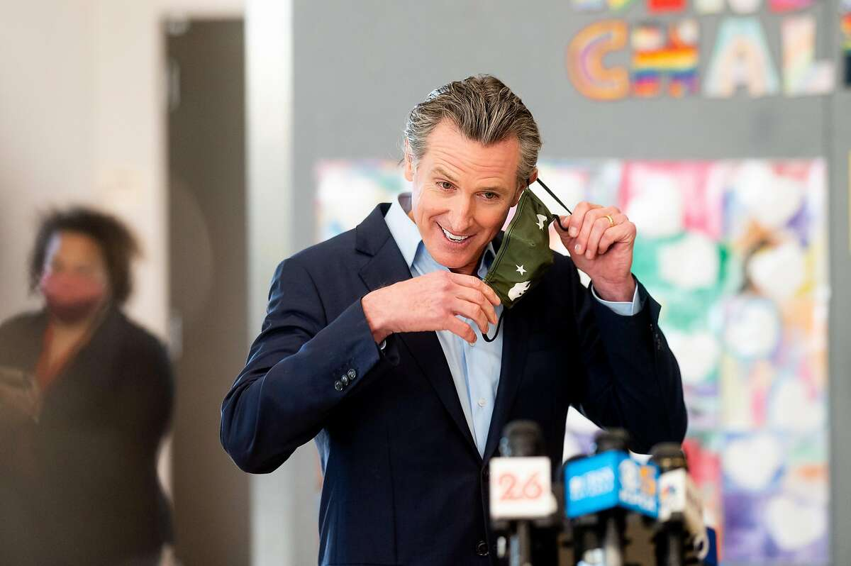 Governor Gavin Newsom removes his mask before speaking at a press conference at Ruby Bridges Elementary School in Alameda, Calif., on Tuesday, March 16, 2021. Newsom and other speakers lauded the Alameda Unified School District for re-opening schools the day before.