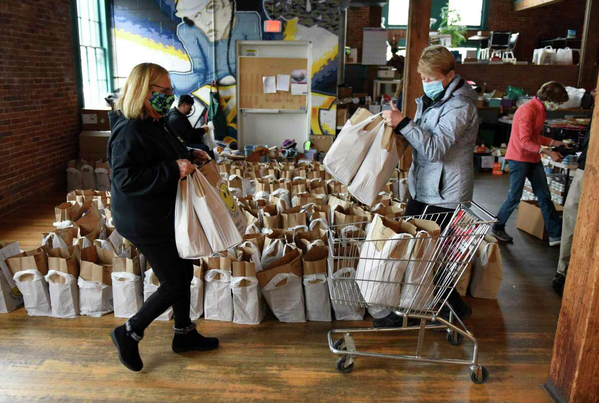 TAG Executive Director Debbie Vetromile, left, loads up a cart with help from a volunteer at the former headquarters of Neighbor to Neighbor at the Arch Street Teen Center in Greenwich, Conn. Monday, Dec. 21, 2020. TAG has been assisting Neighbor to Neighbor's food distribution efforts since March 2020.