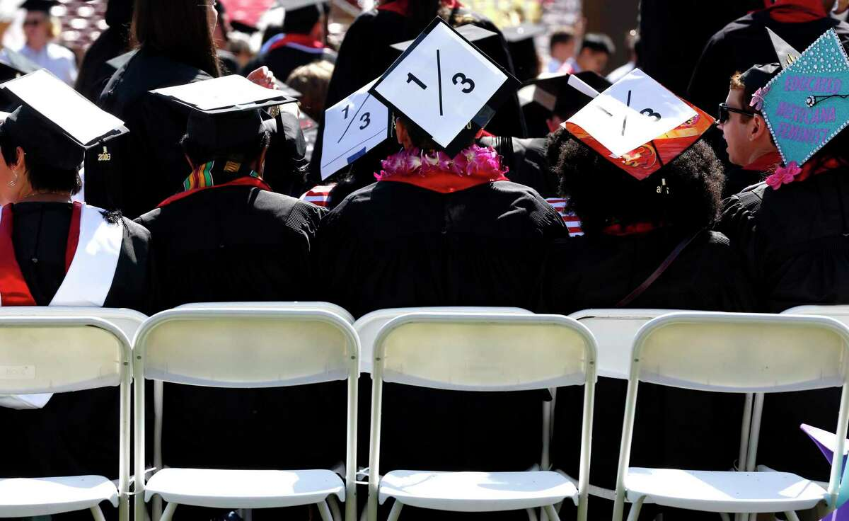 """A Stanford graduates decorate mortarboards with """"1/3,"""" a figure linked to sexual assault against women on campuses."""