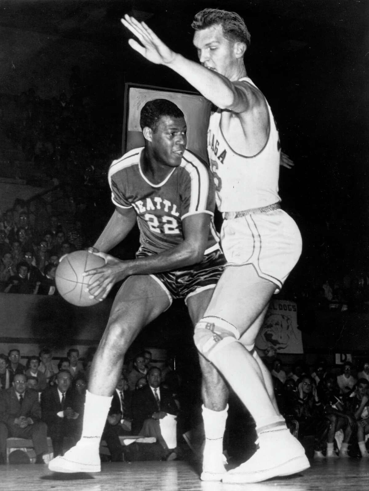 The 6-foot-5 Elgin Baylor (L) playing for Seattle University goes up against 7-foot 3-inch center Jean LaFebvre playing for Gonzaga University in 1958. The following year, Baylor would be serving a 6-month tour of active duty, including time at Fort Sam Houston in San Antonio, before rejoining the Los Angeles Lakers.