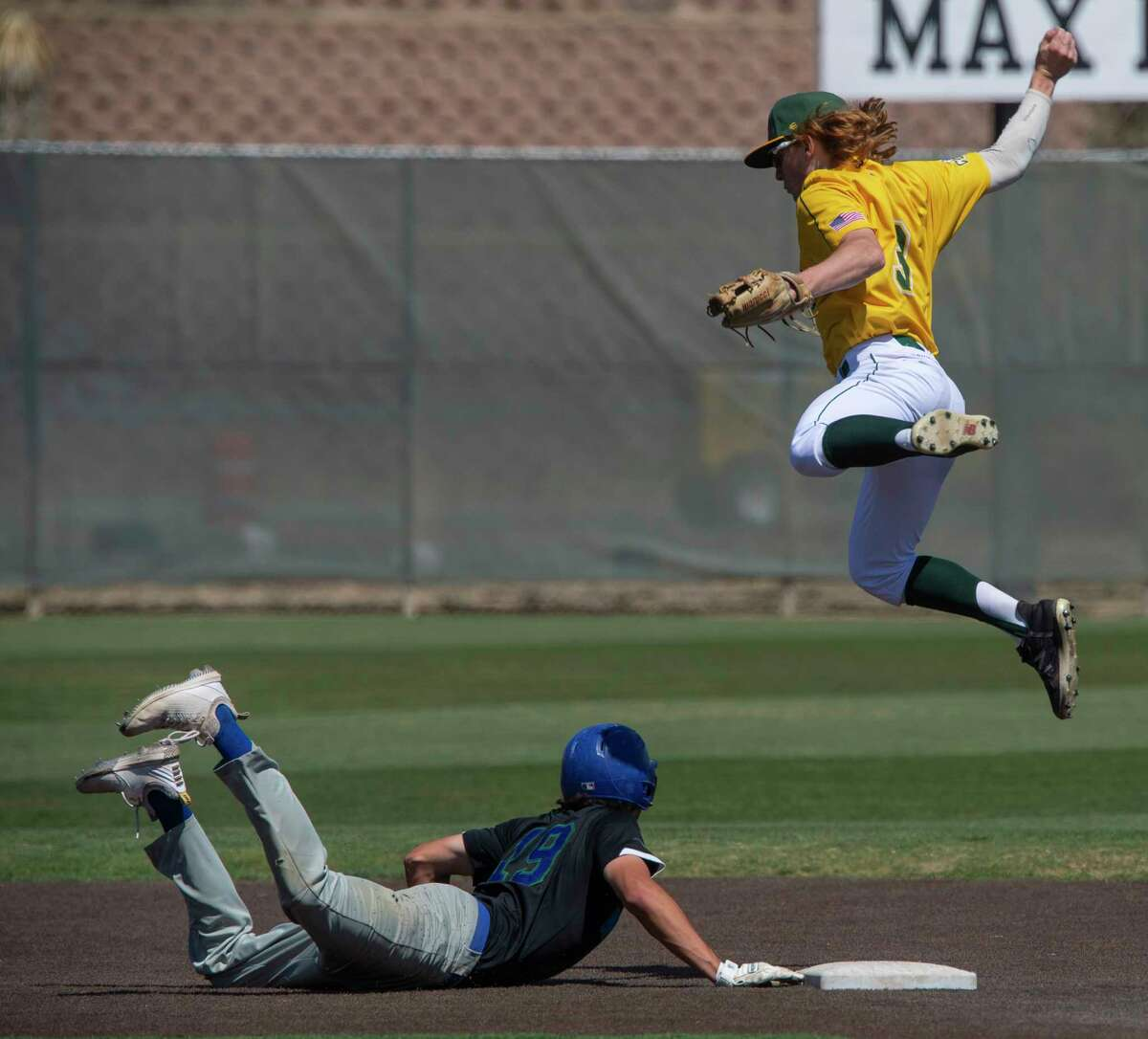 Midland College's Garrett Williams leaps for the throw on a pick-off attempt as Western Texas College's Carson Garza safely dives back to second 03/26/21 at Christensen Stadium. Tim Fischer/Reporter-Telegram