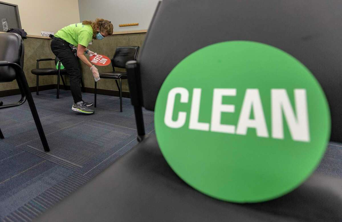 Volunteer Eileen Gaughran cleans chairs at WellMed's Elvira Cisneros Senior Center vaccination clinic on Friday, March 26, 2021. Volunteering at vaccine clinics, often for non-clinical duties, is one way to ethically move up the line to get vaccinated against COVID-19.