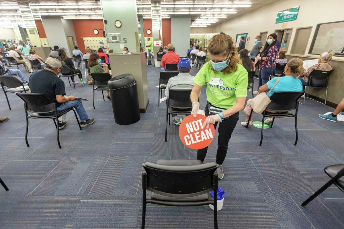 Volunteer Eileen Gaughran cleans chairs on March 26, 2021, at WellMed's Elvira Cisneros Senior Center coronavirus vaccine clinic. Volunteering at vaccine clinics, often for nonclinical duties, is one way to ethically move up the line to get vaccinated against COVID-19.