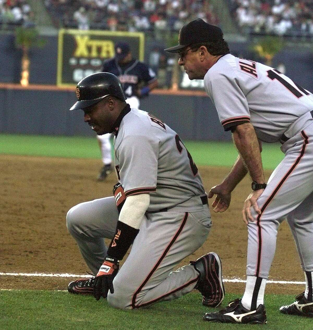 San Francisco Giants' Barry Bonds is assisted by first-base coach Carlos Alfonso after pulling up while running out a ground ball in a 1999 game against the Padres.