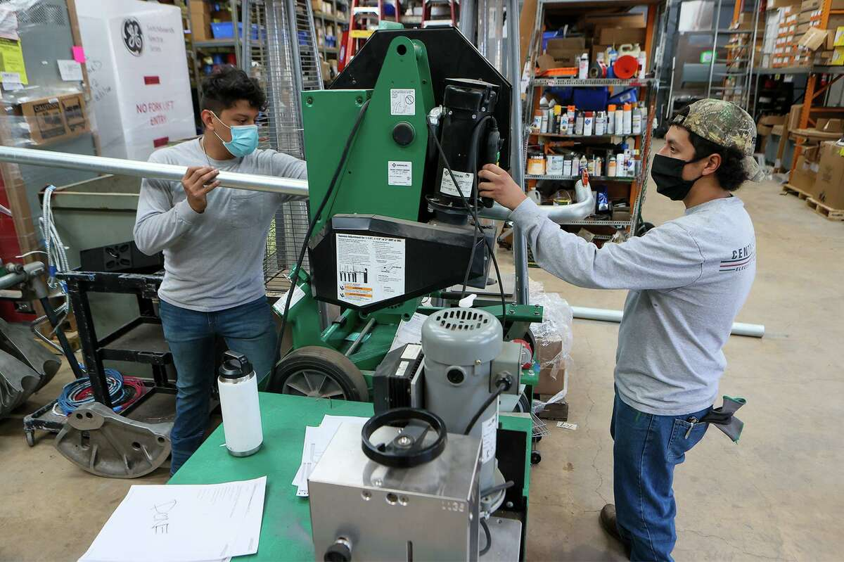 """Brandon Ruiz, left, and Bruno Perez, Workforce Development students from Southside High School, prepare custom conduit in the prefab department at Central Electric, a local electrical contractor, on March 5, 2021. """"A lot of the more timely indicators that we see for March show that that this month will come in quite strong,"""" says Christopher Slijk, associate economist at the Dallas Fed."""