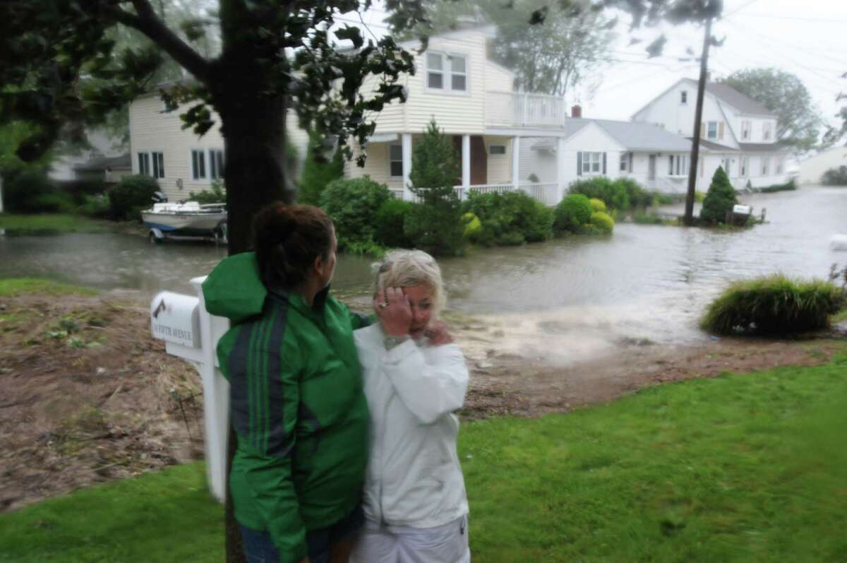 Alberta Murdock, right of Fifth Avenue, is consoled by friend & neighbor Jennifer Marks as she surveys her home in the Hotchkiss Grove section of Branford after the worst of Hurricane Irene passed through the shoreline of Connecticut August 28, 2011.