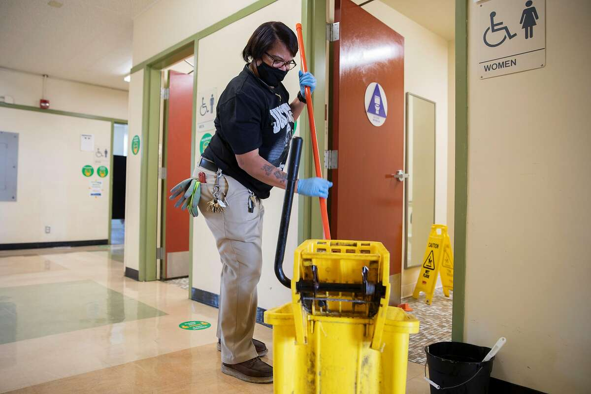 Garfield Elementary School head custodian Antionette Powell disinfects the bathrooms at Garfield Elementary School in Oakland, Calif. Thursday, March 25, 2021. Garfield Elementary School will partially re-open for students in grades kindergarten through second grade beginning Tuesday, March 30.