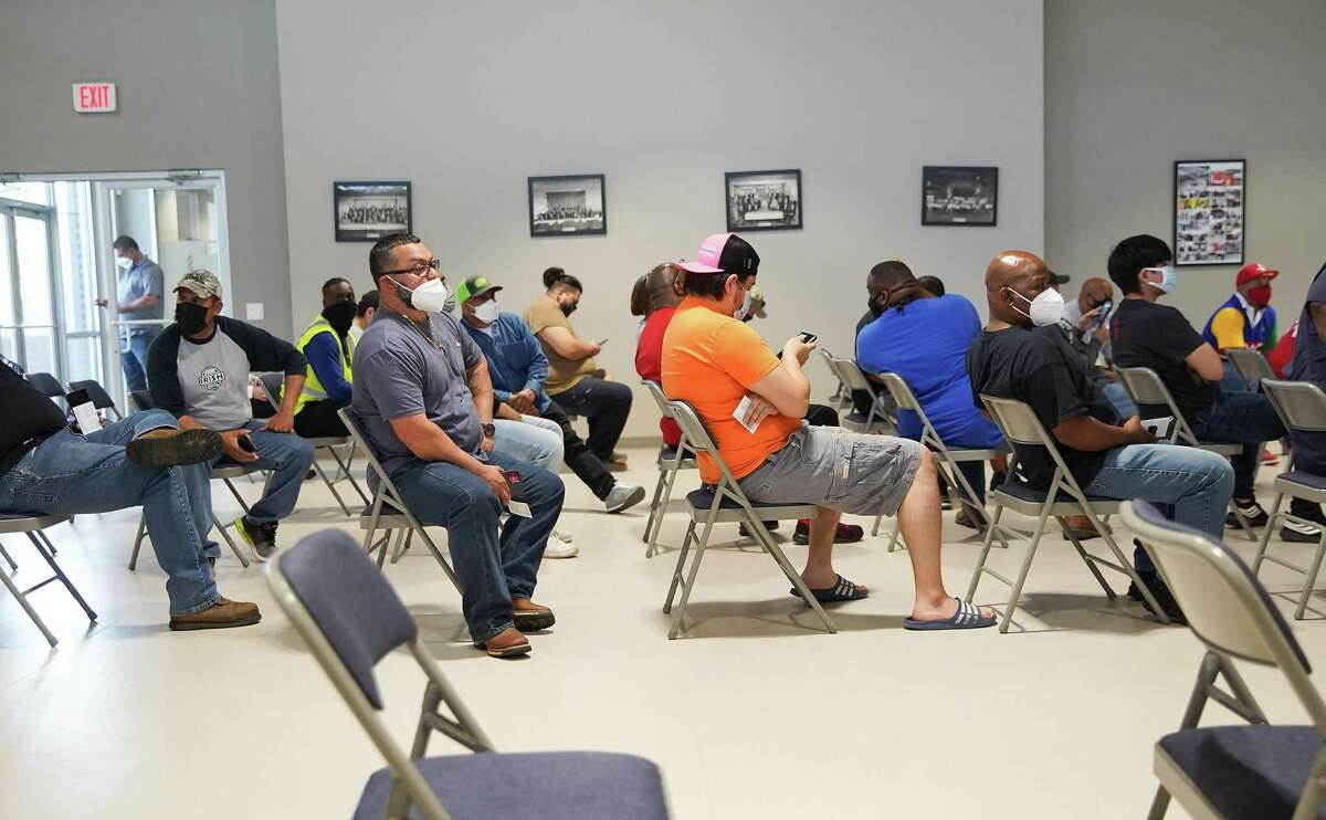 Members of the International Longshoresmen's Union Local 24 wait to get their first dose of the Pfizer vaccine at the union hall in Pasadena, Texas on Tuesday, March 23, 2021. The union coordinated with Harris County Commissioner Adrian Garcia to secure 500 vaccines for their members.