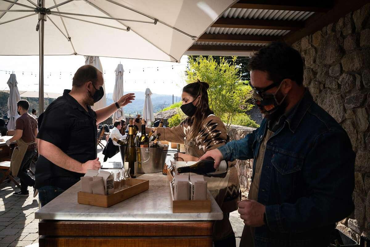 Alex McCart (left), Sabrina Elloway and Justin Pieraldi prepare tasting setups with pre-poured carafes at Robert Sinskey Vineyards in Napa on Feb. 27.