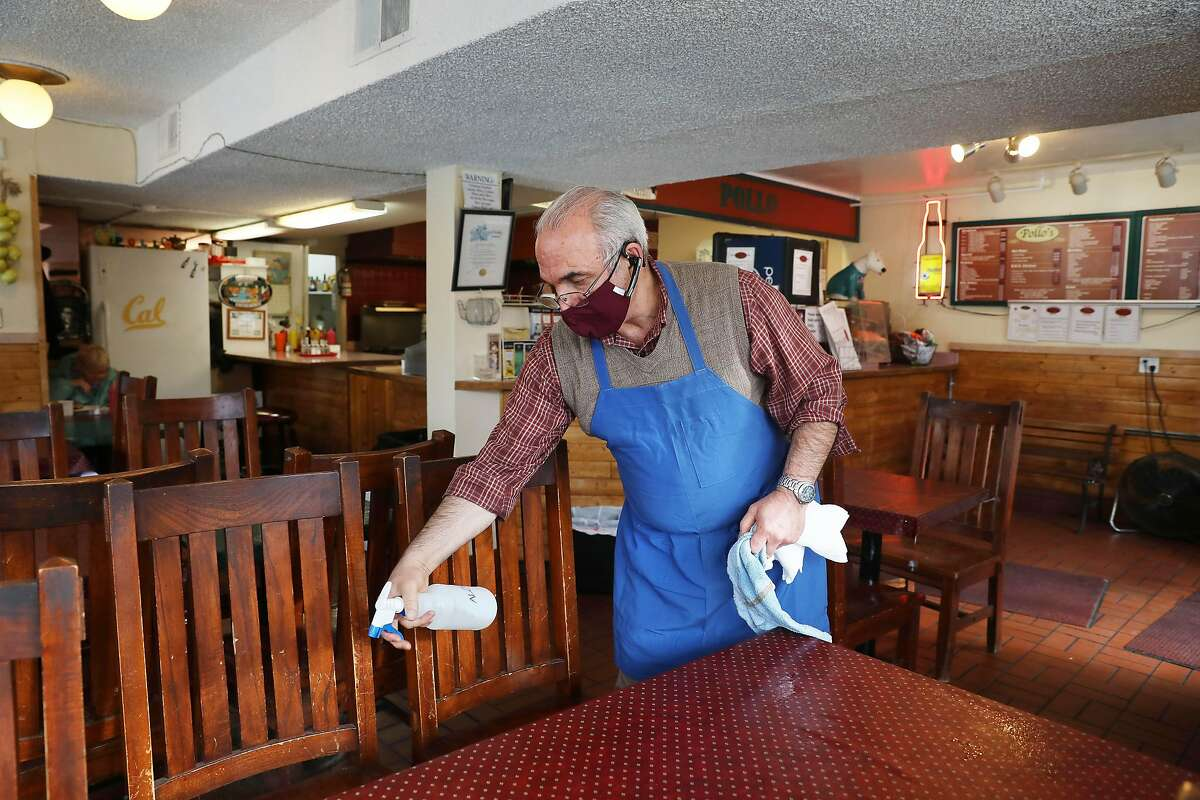 Mostafa Hallaji, owner operator Pollo's, cleans tables and chairs with alcohol on Tuesday, March 9, 2021 in Oakland, Calif.
