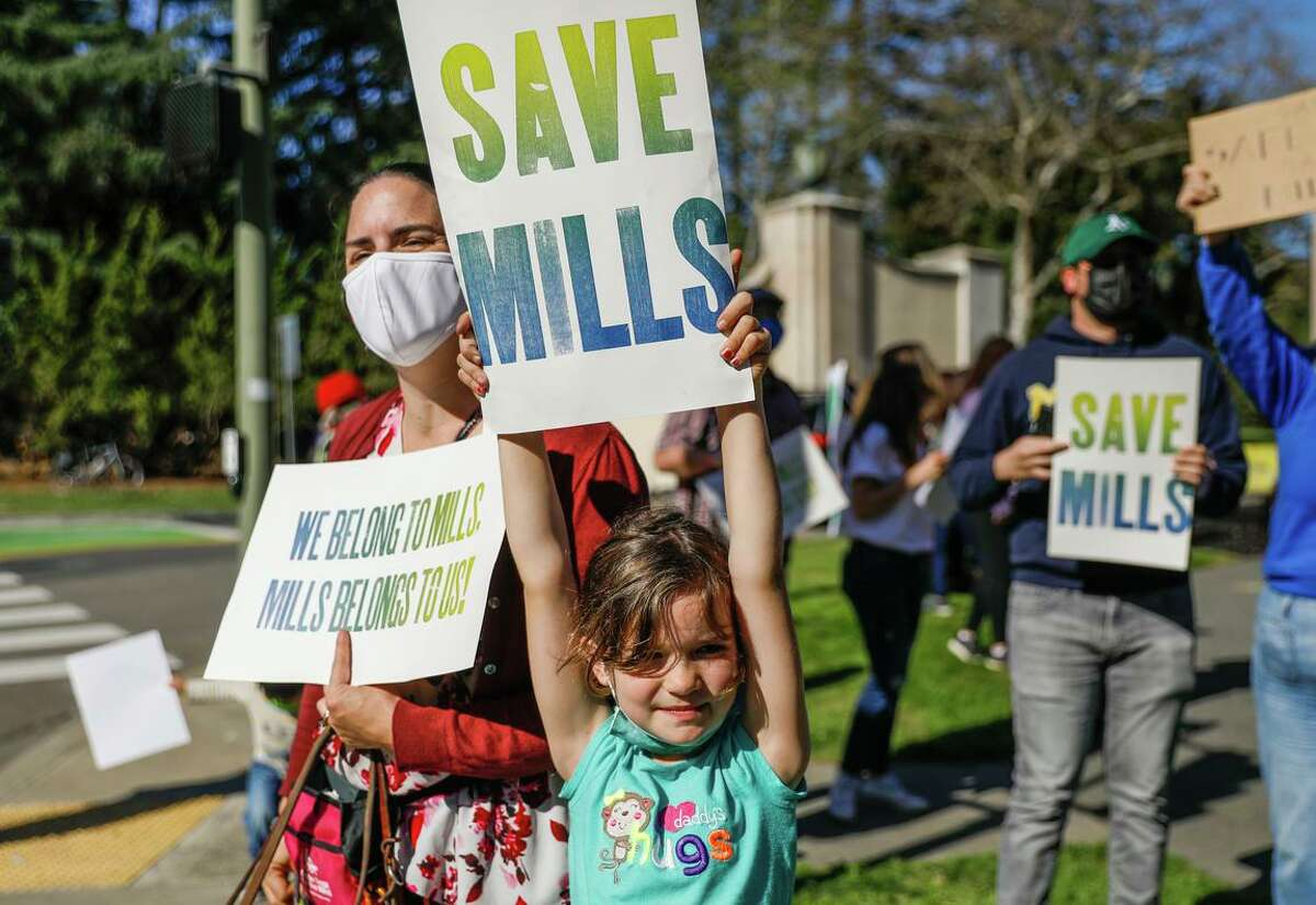 Virginia Prince and daughter Melody Prince,7, rally at the front gate of Mills College which announced it would be shutting down in two years on Friday, March 26, 2021 in Oakland, California. Mills College, a 169-year-old women's college in Oakland, announced it will no long enroll students after the fall, and will shut down in two years. Students and alumnae rallied to get the trustees to change their mind.