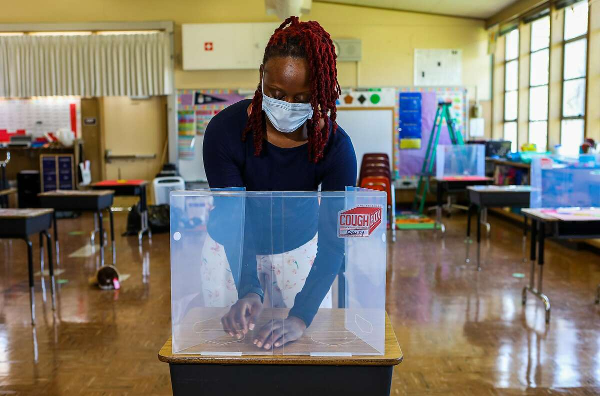 """Teacher Shaione Simmons builds a """"cough box"""" as she prepares her classroom at Madison Park Academy Primary in Oakland."""