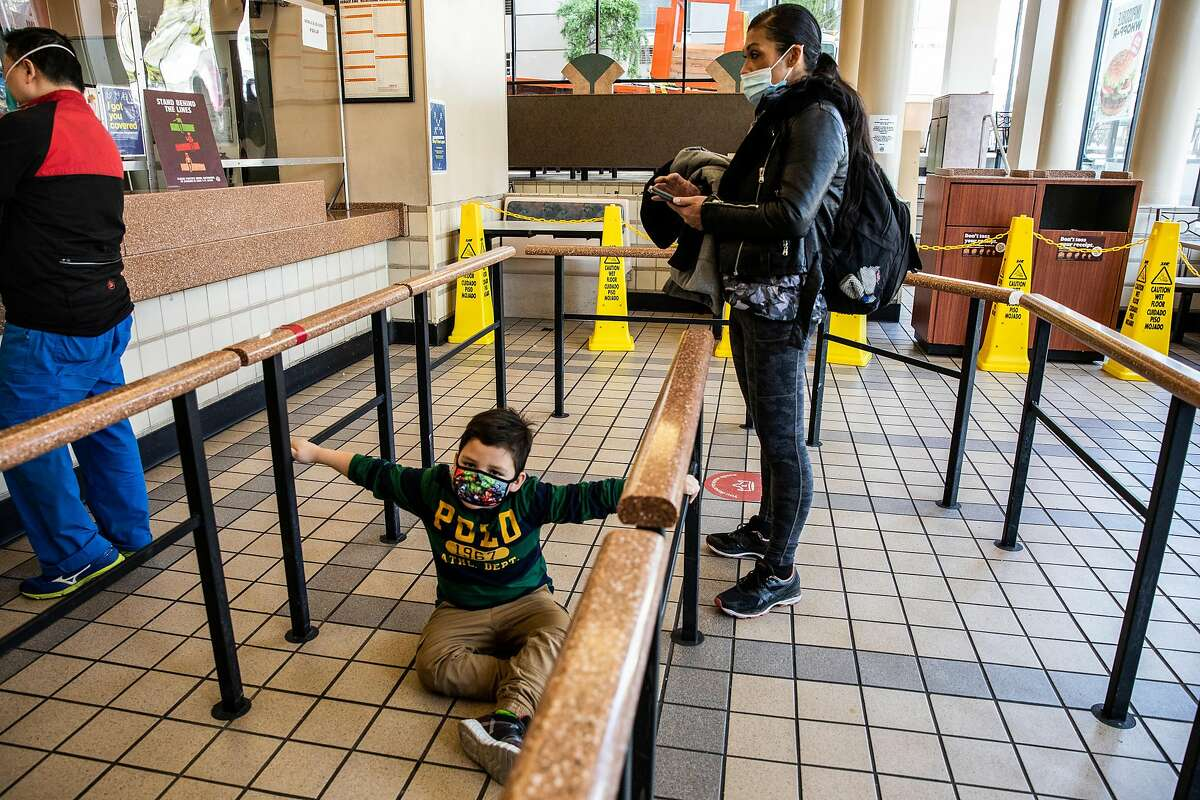 Douglas Jones, 5, briefly sits on the floor inside Burger King as mother Juthaporn Chaloeicheep gets ready to order. Chaloiecheep, a mother of five, was homeless for 20 years.