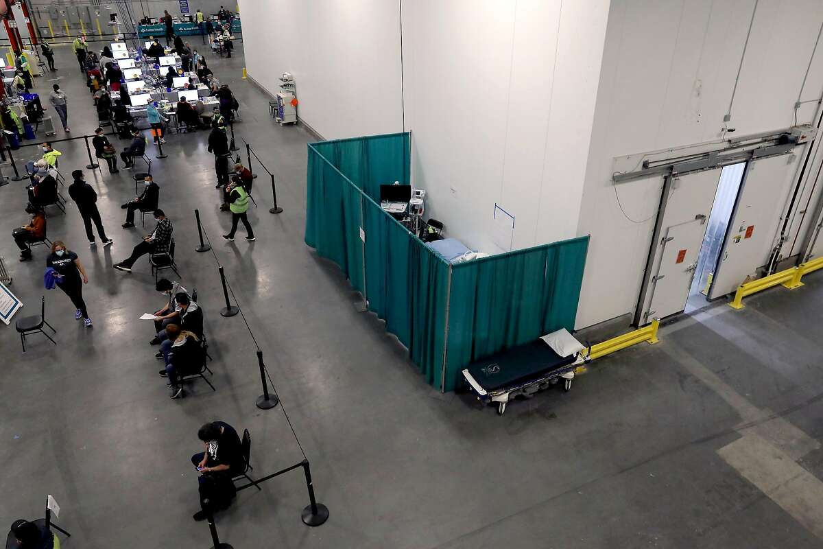 The vaccinarion area, observation area and storage lockers are seen at the vaccine hub inside the previously empty produce warehouse.