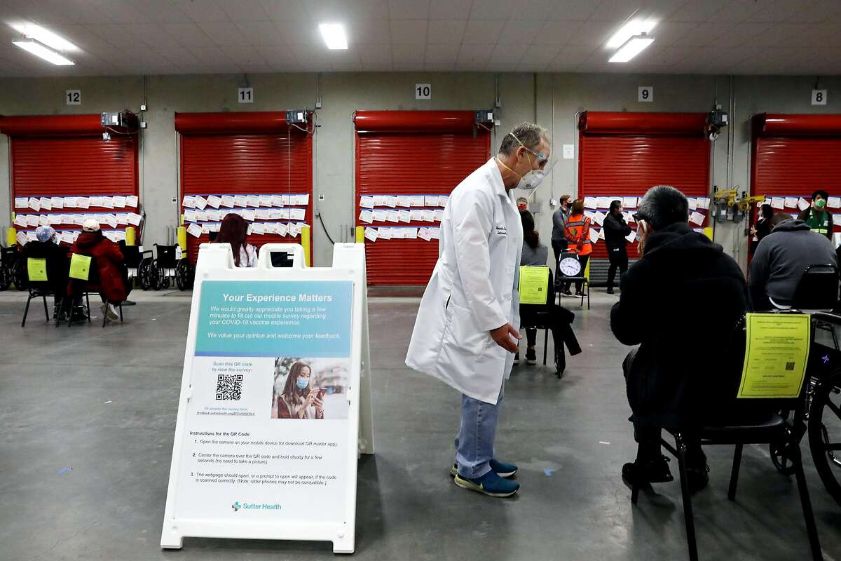 Dr. Howard Edelstein, a Sutter Health infectious disease and internal medicine specialist, works in the observation area at a vaccination hub in a formerly vacant produce warehouse in the Bayview district.