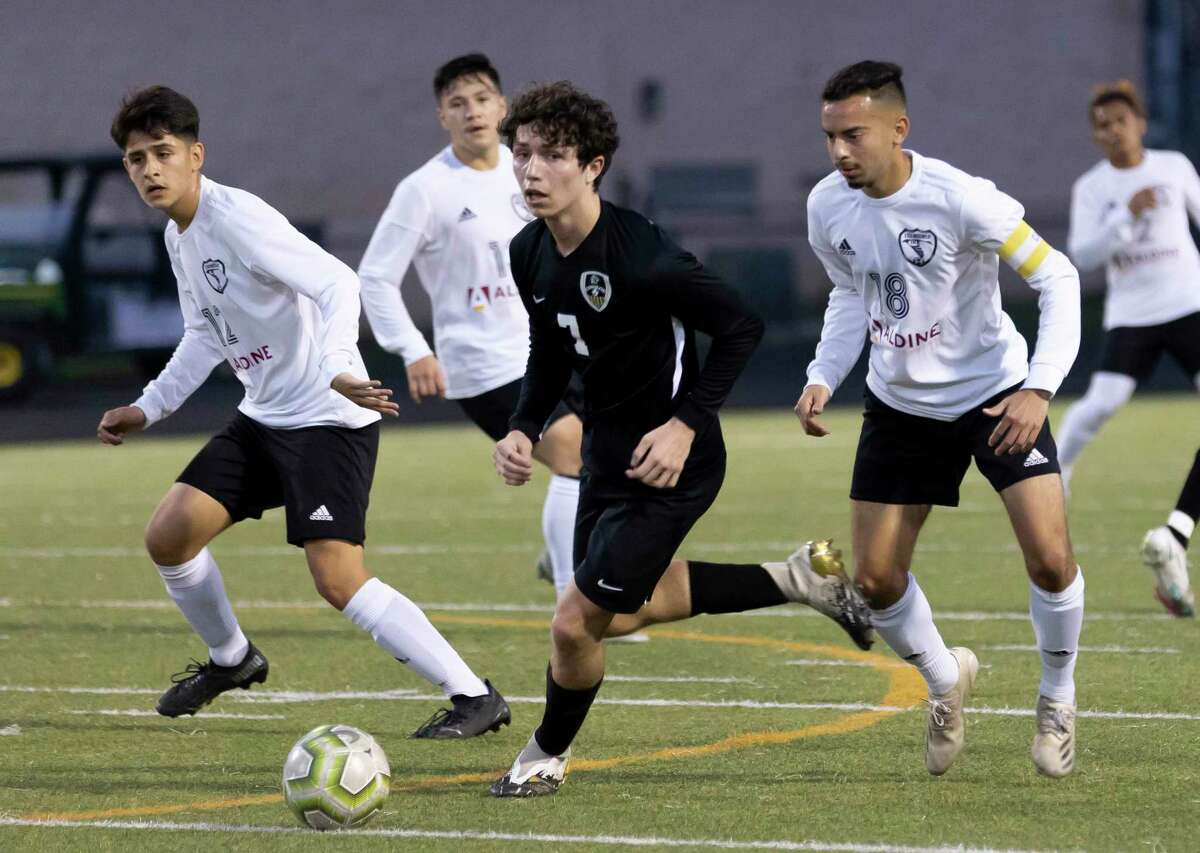 Conroe Dayton Hyde (7) drives the ball while under pressure from multiple Eisenhower players during the first half of a a Region II-6A bi-district boys soccer playoff game at Moorhead Stadium, Friday, March 26, 2021, in Conroe.
