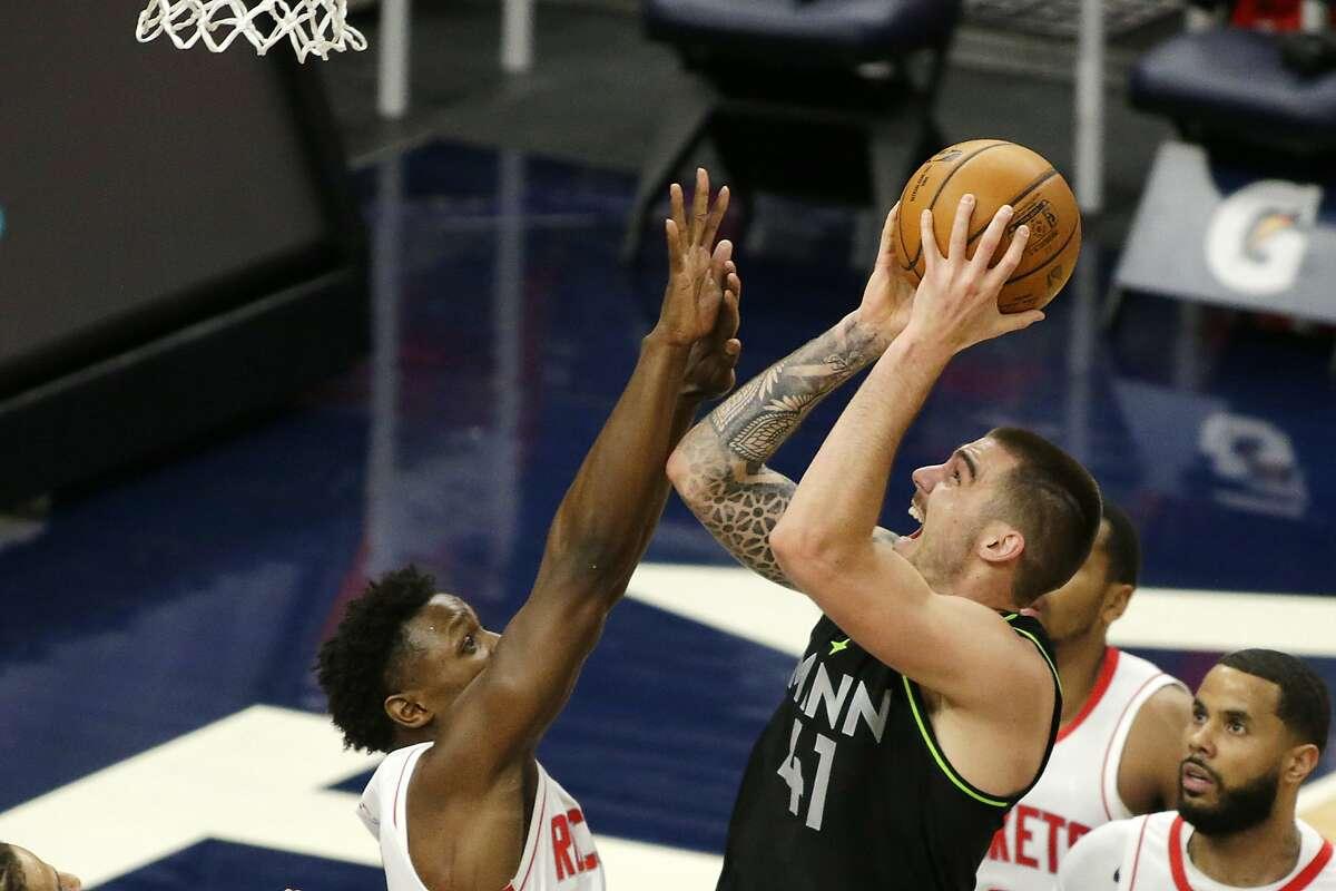 Minnesota Timberwolves forward Juancho Hernangomez (41) shoots against Houston Rockets forward Jae'Sean Tate (8) in the fourth quarter during an NBA basketball game, Friday, March 26, 2021, in Minneapolis. (AP Photo/Andy Clayton-King)
