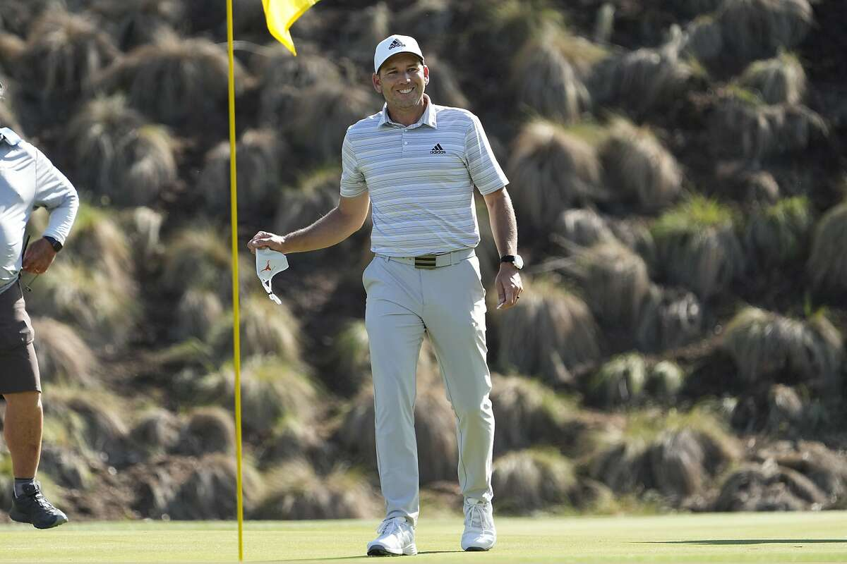 Sergio Garcia, of Spain, takes his ball out of the cup after making a hole in one on the fourth hole to win his playoff against Lee Westwood, of England, during a third round match at the Dell Technologies Match Play Championship golf tournament Friday, March 26, 2021, in Austin, Texas. (AP Photo/David J. Phillip)