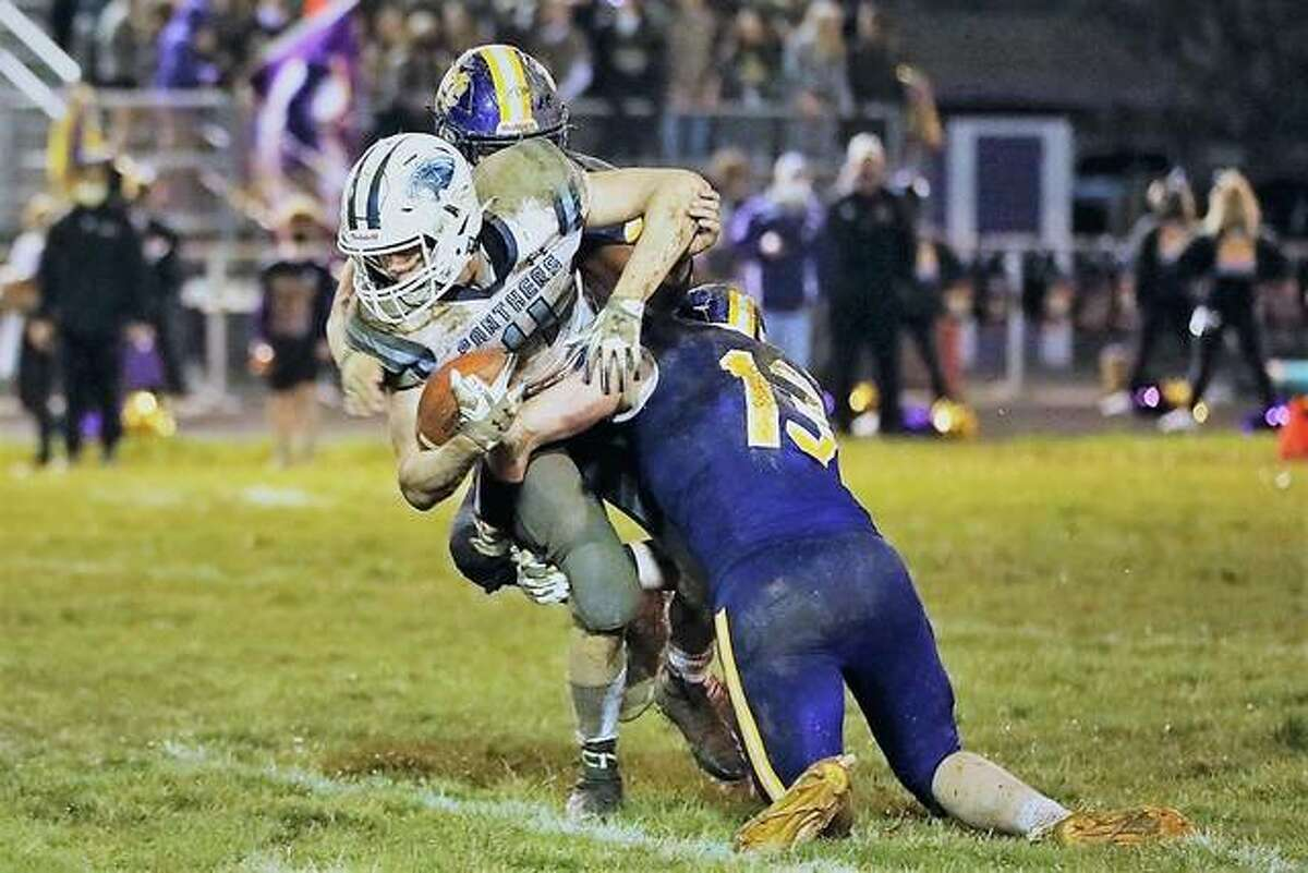 Jersey's Edward Roberts (4) is tackled by Civic Memorial's Dillon Dublo (13) and Briley Christeson (partially hidden) Friday at CM. The Eagles held off Jersey 14-7.