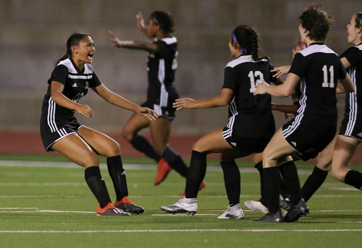 Steele's Noelani Ajel (13) gets rushed by teammates after she scores the deciding penalty kick against Madison during their Class 6A first round girls soccer playoff game at Steele High School on Friday, Mar. 26, 2021. Steele defeated Madison, 3-2, in penalty kicks after two overtime periods.